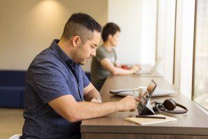 man at desk on tablet